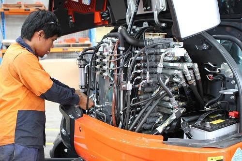 Qualified technician fixing Kubota mini excavator engine