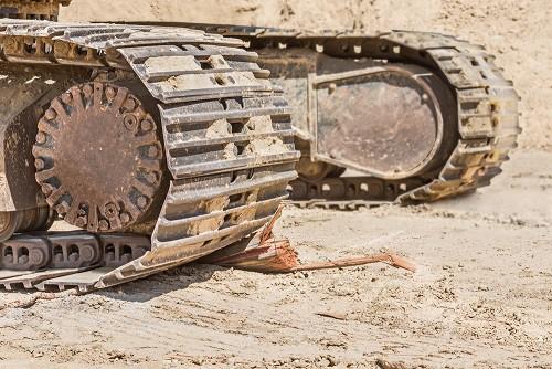 Close up of muddy steel tracks on mini excavator