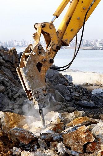 Hydraulic hammer on excavator breaking up large rocks.